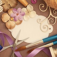 craft supplies: scissors, paint brushes, paper, buttons, ribbon and flowers.